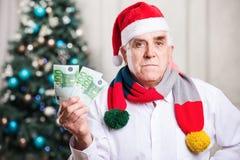 拿着金钱的圣诞老人的帽子的老人 库存照片