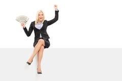 拿着金钱的快乐的女实业家供以座位在盘区 免版税库存图片