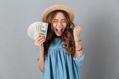 拿着金钱的快乐的妇女 闭合的眼睛 免版税库存图片