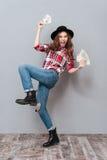 拿着金钱的快乐的年轻深色的夫人 库存照片