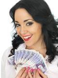 拿着金钱的愉快的可爱的富裕的少妇 免版税库存图片