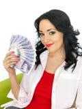 拿着金钱的愉快的富裕的可爱的年轻西班牙妇女 免版税库存照片