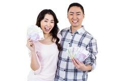拿着金钱的愉快的快乐的夫妇画象  库存图片