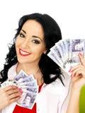 拿着金钱的愉快的美丽的富有的年轻西班牙妇女 免版税图库摄影
