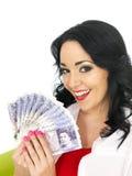 拿着金钱的愉快的美丽的富裕的年轻西班牙妇女 免版税库存图片