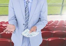 拿着金钱的腐败商人的中间部分在体育场内 免版税库存照片