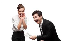 拿着金钱的年轻愉快的商人 免版税库存照片