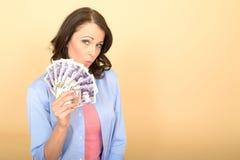 拿着金钱的年轻愉快的妇女看起来喜欢和高兴 免版税库存照片