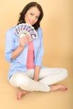 拿着金钱的年轻愉快的妇女看起来喜欢和高兴 免版税图库摄影