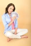 拿着金钱的年轻愉快的妇女看起来喜欢和高兴 库存图片