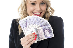 拿着金钱英镑磅的微笑的可爱的少妇 免版税库存照片