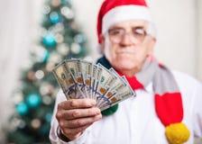 拿着金钱,手的圣诞老人的帽子的人在焦点 免版税库存图片