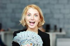 拿着金钱以欢欣的女实业家 免版税库存照片