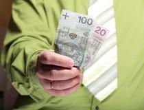 拿着金钱100波兰兹罗提的商人 免版税图库摄影