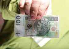 拿着金钱100波兰兹罗提的商人 免版税库存图片