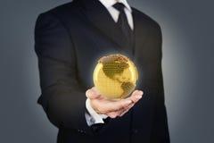 拿着金黄地球的商人 免版税库存图片