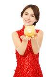 拿着金黄存钱罐的亚裔妇女 中国新年好 免版税库存照片
