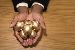 拿着金黄鸡蛋的人 免版税库存图片