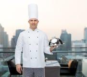 拿着钓钟形女帽的愉快的男性厨师厨师 免版税库存图片