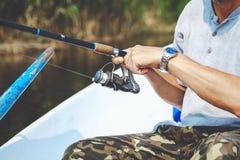 拿着钓鱼竿和卷轴把柄的手渔夫被转动 图库摄影