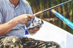 拿着钓鱼竿和卷轴把柄的手渔夫被转动 免版税图库摄影