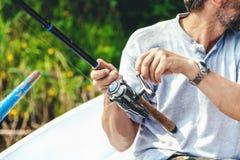 拿着钓鱼竿和卷轴把柄的手渔夫被转动 免版税库存图片