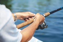 拿着钓鱼竿和卷轴把柄的手渔夫被转动 免版税库存照片