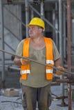 拿着钢棍的建筑工人 免版税图库摄影