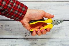 拿着钳子工具的男性收养手中 免版税库存图片
