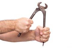 拿着钳子的手 免版税库存图片