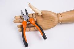拿着钳子的木手 库存照片