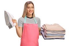 拿着铁和堆被电烙的和被包装的衣裳的妇女 免版税库存照片