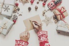 拿着铅笔和写信件愿望的手给圣诞老人cla 图库摄影