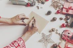 拿着铅笔和写信件愿望的手给圣诞老人cla 免版税库存照片