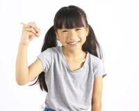 拿着铅笔的愉快的女孩 免版税库存图片