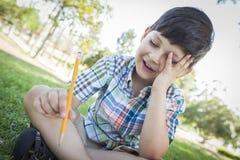 拿着铅笔的沮丧的逗人喜爱的年轻男孩坐草 免版税图库摄影