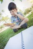 拿着铅笔的沮丧的逗人喜爱的年轻男孩坐草 免版税库存图片