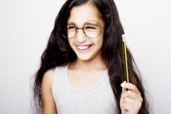 拿着铅笔的玻璃的一个美丽的孩子女孩手中 库存图片