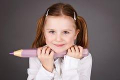 拿着铅笔的逗人喜爱的年轻女小学生 免版税库存图片