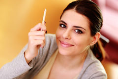 拿着铅笔的年轻微笑的妇女 库存图片