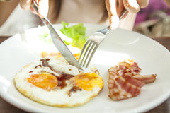 拿着银器焦点鸡蛋的早餐手 库存照片