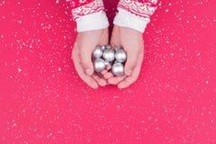 拿着银色圣诞节中看不中用的物品的儿童手 免版税图库摄影