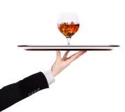 拿着银色盘子用白兰地酒的侍者 图库摄影
