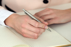 拿着银色笔的妇女手准备好做在被打开的noteb的笔记 免版税库存照片