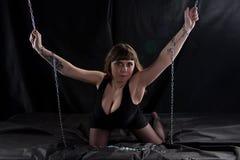 拿着链子的弯曲的妇女的图象 免版税库存照片
