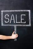 拿着销售标志的手被画在黑板 免版税库存图片