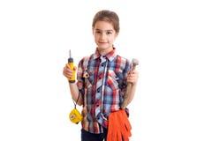 拿着锤子、螺丝刀和轮盘赌的小女孩 免版税库存照片