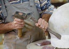 拿着锤子和凿子的手 免版税库存照片