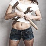 拿着锤子和板钳扳手的性感的女孩 免版税库存照片