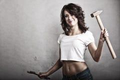 拿着锤子和板钳扳手的性感的女孩 图库摄影